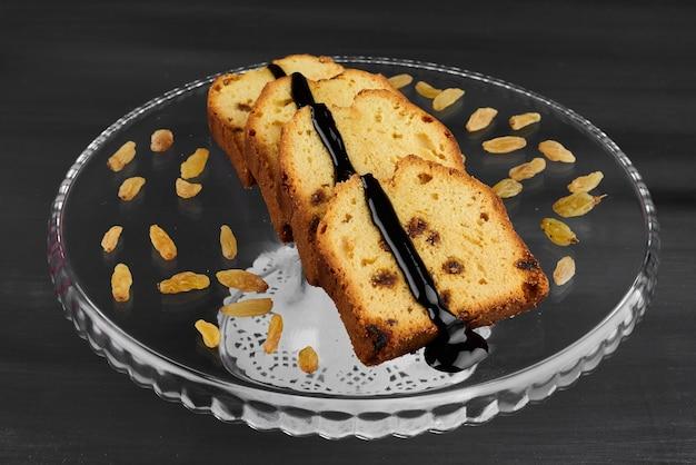 Schokoladenkuchenscheiben auf einer glasplatte mit sultanine.