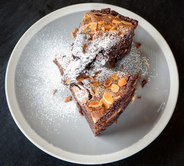 Schokoladenkuchenstück auf dem tisch stück schokoladenkuchenkakao mit nuss- und puderzucker
