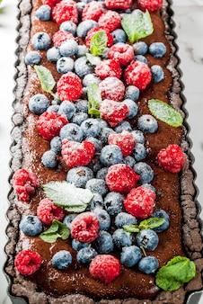 Schokoladenkuchentörtchen mit schokoladencreme und frischen rohen beeren