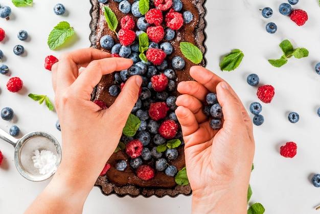 Schokoladenkuchentörtchen mit schokoladencreme und frischen sommerbeeren