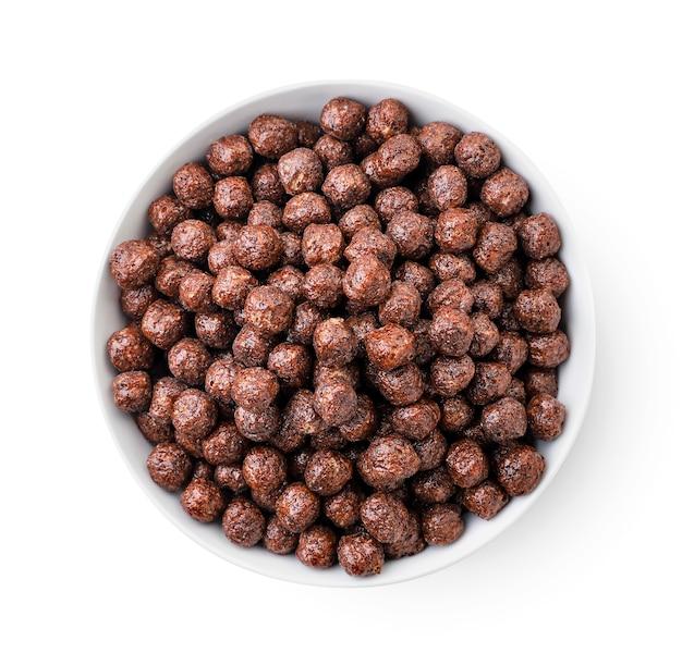 Schokoladenkugeln in einer plattennahaufnahme auf weißem hintergrund, trockenes frühstück. isoliert, ansicht von oben