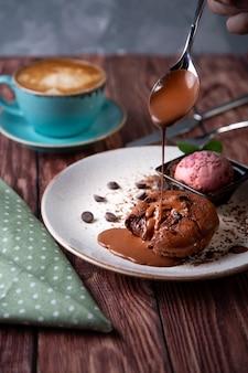 Schokoladenlava-kuchen geschmolzen mit eiscreme auf platte und cappuccino. kugeln eis in der tasse. dunkles schwarz .
