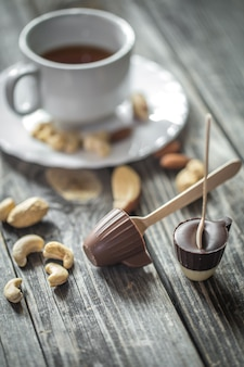 Schokoladenlutscher in form einer kleinen tasse mit einer tasse tee und nüssen auf holz