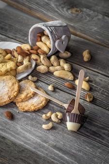 Schokoladenlutscher in form einer kleinen tasse und verschiedener nüsse in einem eimer auf holz