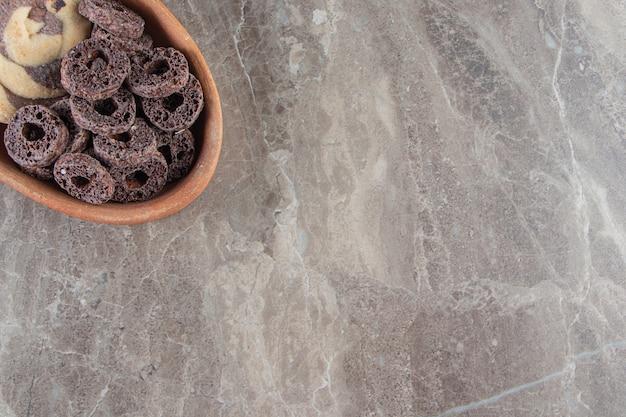 Schokoladenmaisringe und -plätzchen in einer schüssel auf marmor.