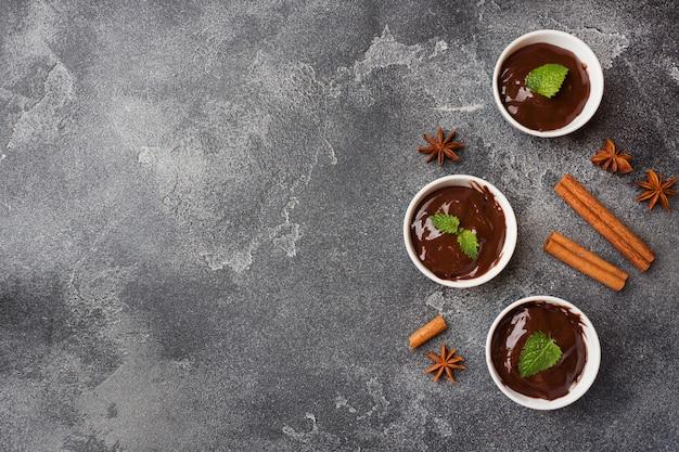 Schokoladenmasse mit minze, zimt und anis auf dunklem hintergrund