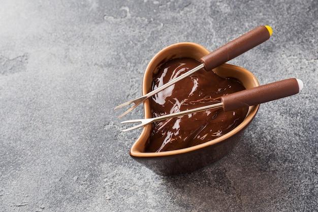 Schokoladenmasse mit zimt und anis. fondue mit schokolade auf einer dunklen konkreten tabelle.