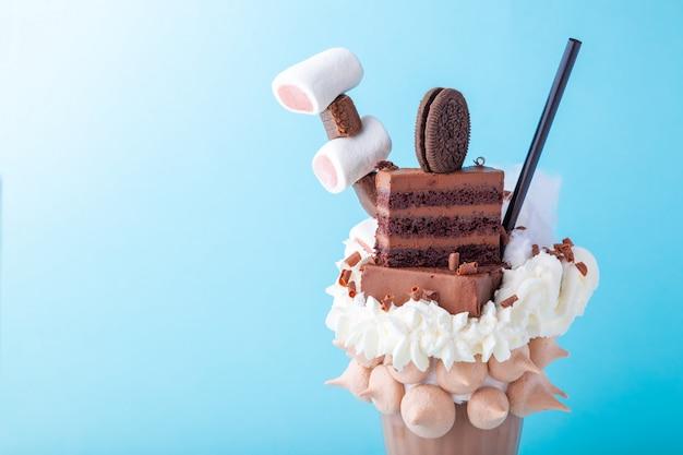 Schokoladenmilch-freakshake mit schlagsahne, marshmallow, kuchen, keks