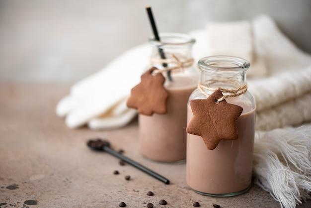Schokoladenmilch mit keksen und warmem strickschal auf dem tisch