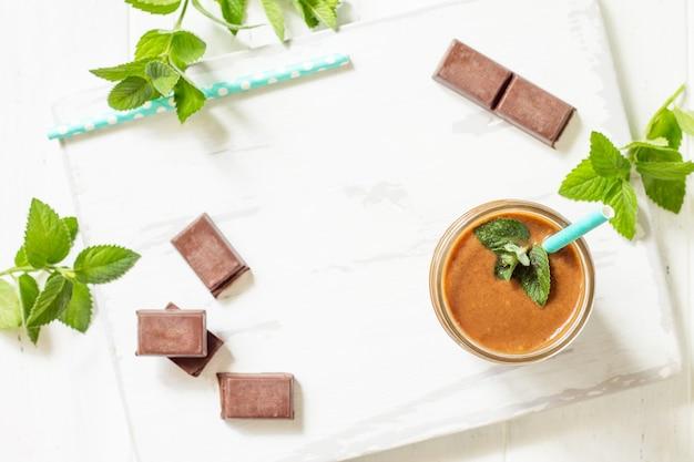 Schokoladenmilchshake oder smoothies auf weißem holzhintergrund gesundes saftiges vitamingetränk