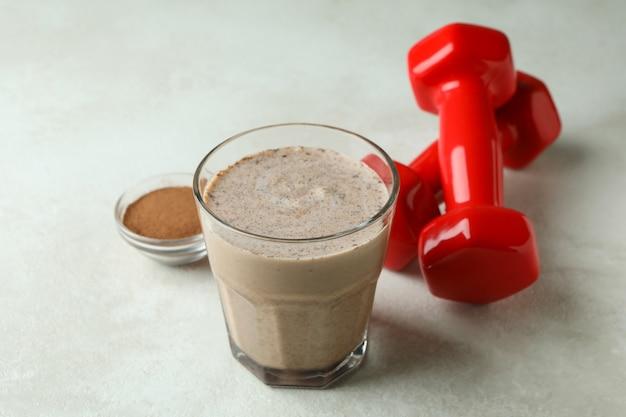 Schokoladenmilchshake, schokoladenpulver und hanteln auf weiß strukturiertem tisch