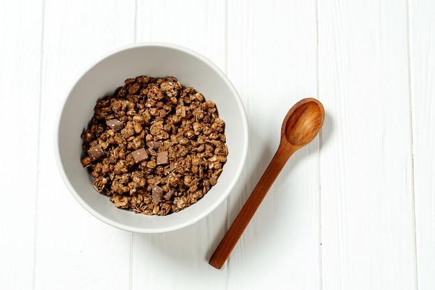Schokoladenmüsli in einer weißen schüssel in einer zusammensetzung mit einem löffel auf weißem hölzernem hintergrund.