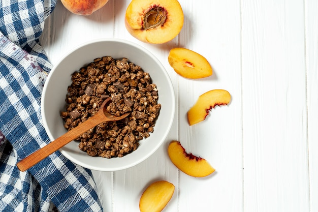 Schokoladenmüsli in einer weißen schüssel in einer zusammensetzung mit einem löffel und pfirsich auf weißem hölzernem hintergrund.