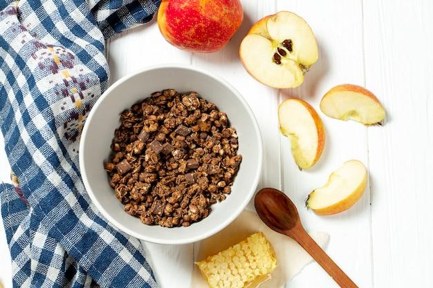 Schokoladenmüsli in einer weißen schüssel in einer zusammensetzung mit waben, einem löffel, apfel auf weißem hölzernem hintergrund.