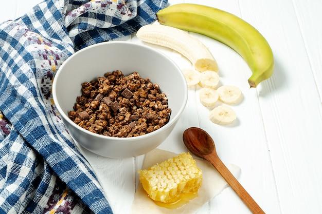 Schokoladenmüsli in einer weißen schüssel in einer zusammensetzung mit waben, einem löffel, banane auf weißem hölzernem hintergrund.