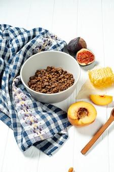 Schokoladenmüsli in einer weißen schüssel in einer zusammensetzung mit waben, einem löffel, feigen und pfirsich.