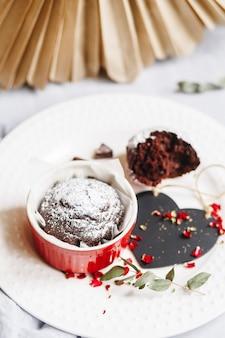 Schokoladenmuffin in roter tasse. mockup-valentinsgruß-schwarzes herzexemplar. kleines glasiertes keramik-auflaufförmchen mit braunem kuchen auf weißem hintergrund.