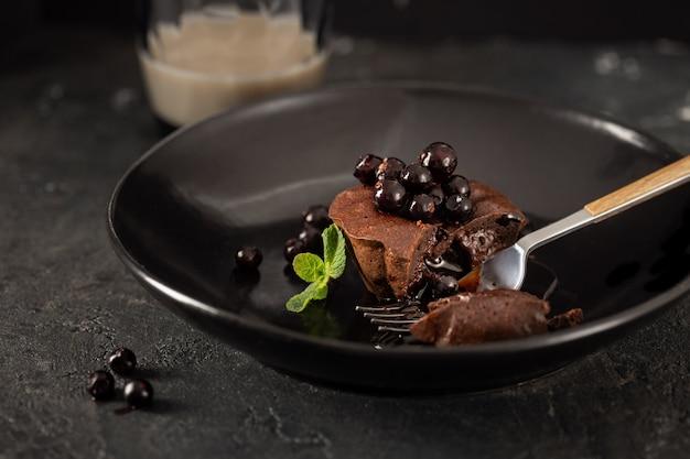 Schokoladenmuffin mit blaubeeren in der schwarzen platte auf dunklem hintergrund mit kaffee