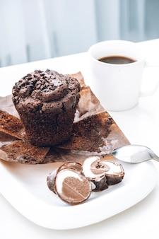 Schokoladenmuffin mit eis und schwarzem kaffee zum frühstück. schokoladenkuchen.