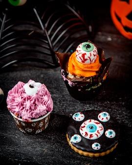 Schokoladenmuffin mit orangencreme und halloween-keksen