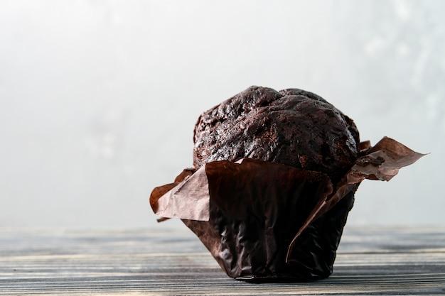 Schokoladenmuffin oder muffin auf einem grauen hölzernen hintergrund.