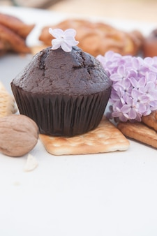Schokoladenmuffin und fliederfoto, vertikal