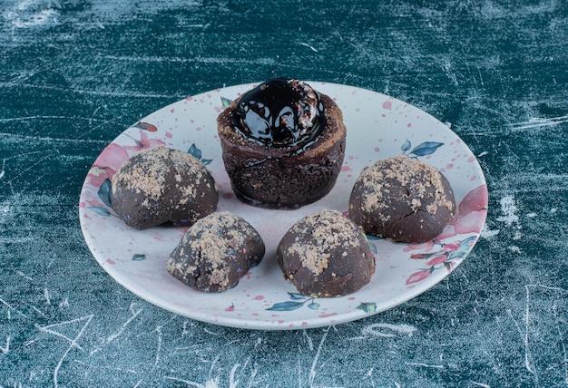 Schokoladenmuffins auf dem teller, auf dem blauen hintergrund