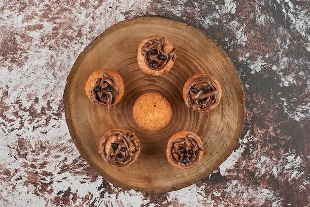 Schokoladenmuffins auf einem holzbrett.
