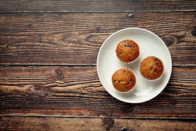 Schokoladenmuffins auf einen runden weißen teller legen