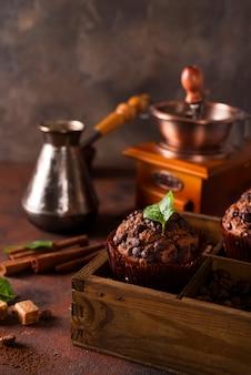 Schokoladenmuffins auf einer holzkiste mit körnern von kaffee und gewürzen,