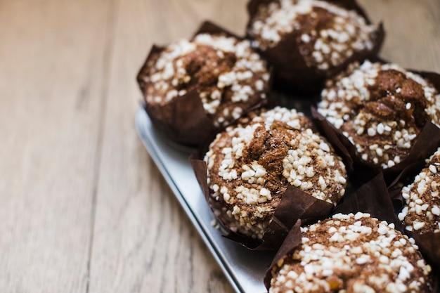 Schokoladenmuffins im papierhalter des kleinen kuchens auf hölzernem hintergrund
