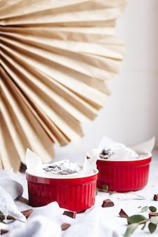 Schokoladenmuffins in roten tassen. kleines glasiertes keramikförmchen mit braunen kuchen auf grauem und weißem hintergrund.