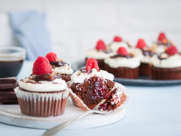 Schokoladenmuffins, kleiner kuchen auf dem tisch geschnitten zur hälfte mit einem tasse kaffee und frischen himbeeren