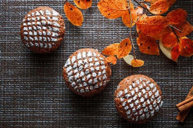 Schokoladenmuffins mit apfelfüllung auf einem hintergrund von herbstblättern und zimt