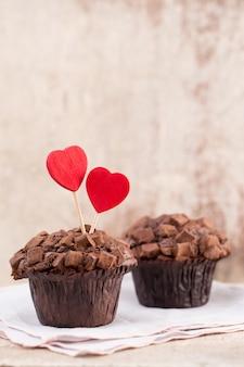 Schokoladenmuffins mit herz auf rustikalem holztisch