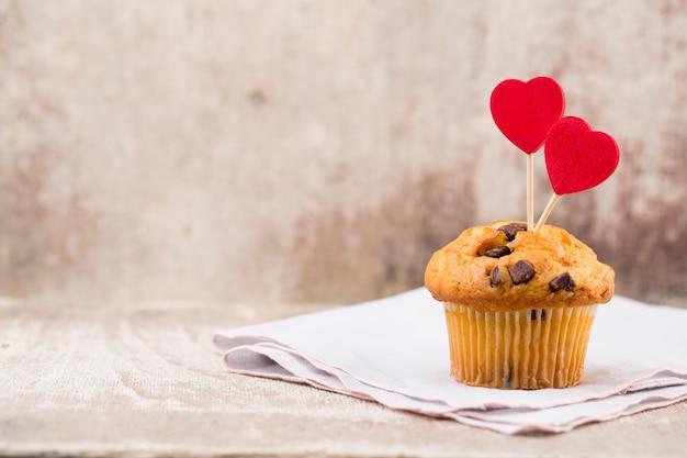 Schokoladenmuffins mit herzweinlesehintergrund, selektiver fokus.