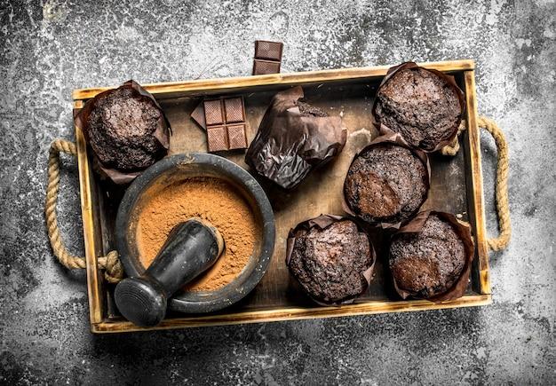 Schokoladenmuffins mit kakao auf altem tablett auf rustikalem tisch.