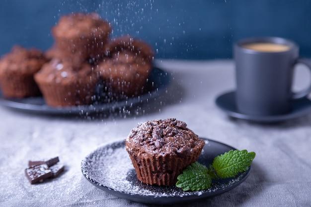 Schokoladenmuffins mit minze auf einem schwarzen teller, mit puderzucker bestreut. hausgemachtes backen. im hintergrund eine tasse kaffee und ein teller mit muffins. blauer hintergrund.