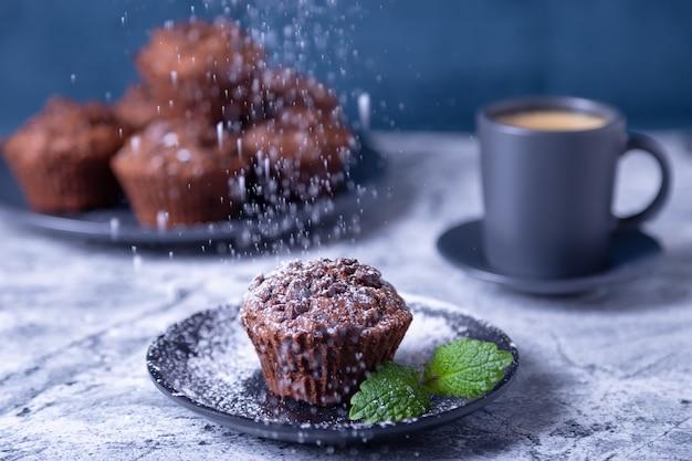 Schokoladenmuffins mit minze auf einem schwarzen teller, mit puderzucker bestreut. hausgemachtes backen. im hintergrund eine tasse kaffee und ein teller mit muffins. marmortisch und blauer hintergrund.