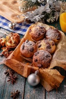 Schokoladenmuffins mit puderzucker auf dem holztisch, rustikale art