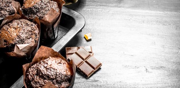 Schokoladenmuffins mit schokoladenstücken. auf der schwarzen tafel.
