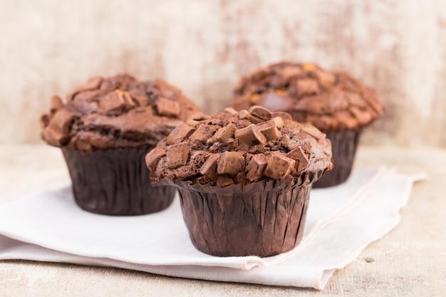 Schokoladenmuffins mit schokoladenweinlesehintergrund, selektiver fokus.