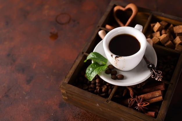 Schokoladenmuffins mit tasse kaffee auf einer holzkiste mit körnern des kaffees und der gewürze