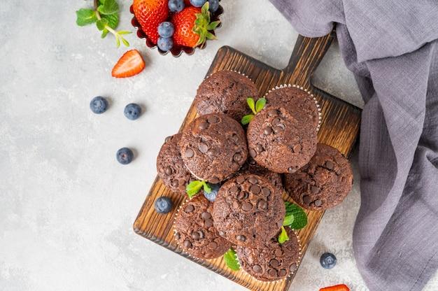 Schokoladenmuffins oder cupcakes mit schokoladentropfen auf einem holzbrett mit frischen beeren und minze.