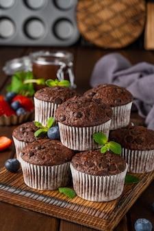 Schokoladenmuffins oder cupcakes mit schokoladentropfen auf einem holzbrett mit frischen beeren und minze