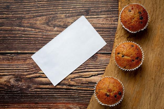 Schokoladenmuffins und leeres weißes papier auf holzboden gelegt