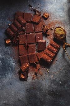 Schokoladenmuster. milchschokolade, sternanis und kakaopulver auf grauem hintergrund