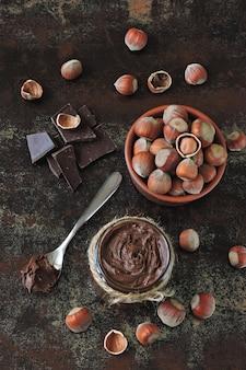 Schokoladennusspaste und ungeschälte haselnüsse.