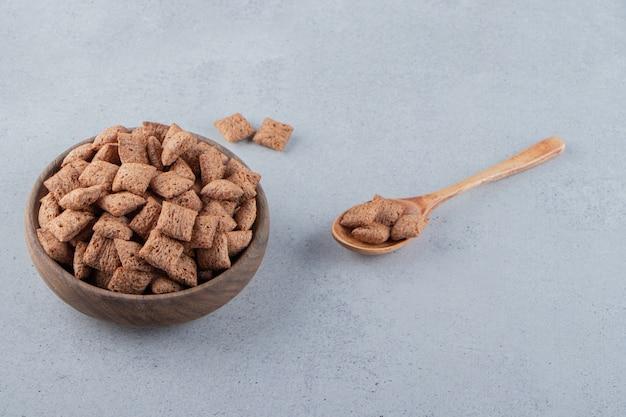 Schokoladenpads cornflakes in holzschale auf steinhintergrund. foto in hoher qualität
