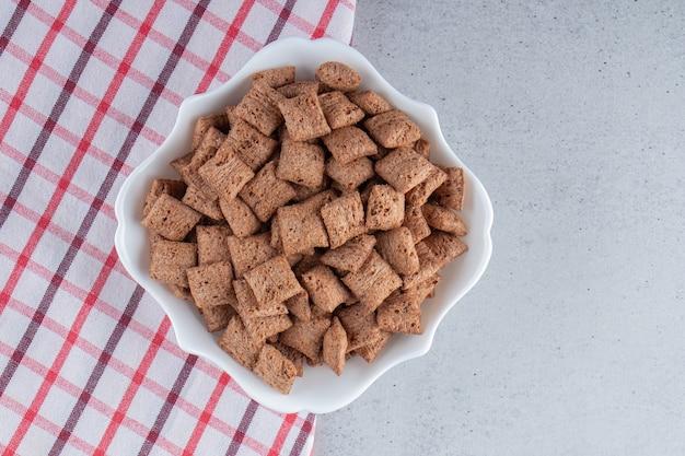 Schokoladenpads cornflakes in weißer schüssel auf steinhintergrund. foto in hoher qualität